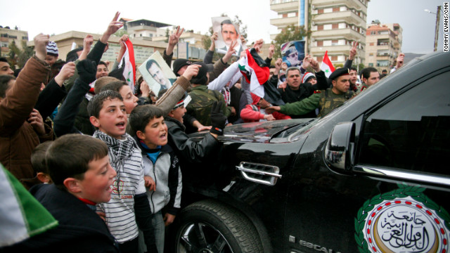 Pro-Assad supporters surround Arab League monitors as they leave Kisweh.