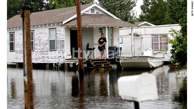 A man looks at flood waters from his home in Lafitte, Louisiana.