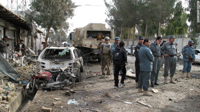 Afghan policemen investigate the scene of the attack in Lashkar Gah on Thursday.