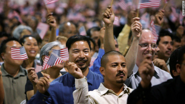 Immigrants wave flags after being sworn in as U.S. citizens in naturalization ceremonies in Pomona, California.