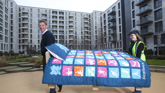 British rowing legend Matthew Pinsent helps lift in the first of 16,000 beds to be installed in London's Olympic Village on January 26, 2012.