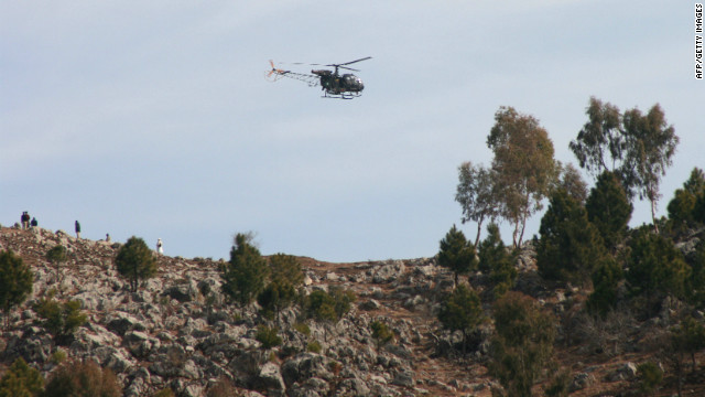 Pakistani security officials and an army helicopter search Friday a hilly area following a rockets attack in Abbottabad.