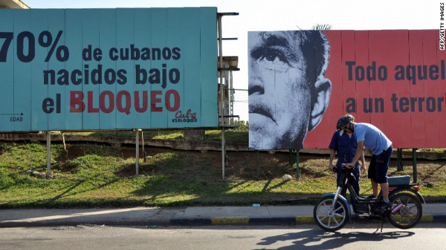 In Cuba, a man checks his motorcycle in front of political billboards that allude to the US embargo on Cuba