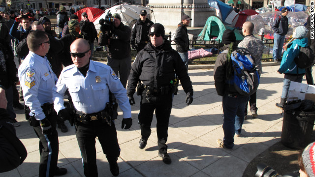 Police walk through the McPherson Square camp of Occupy DC on Monday. Demonstrators greeted them with jeers and taunts.