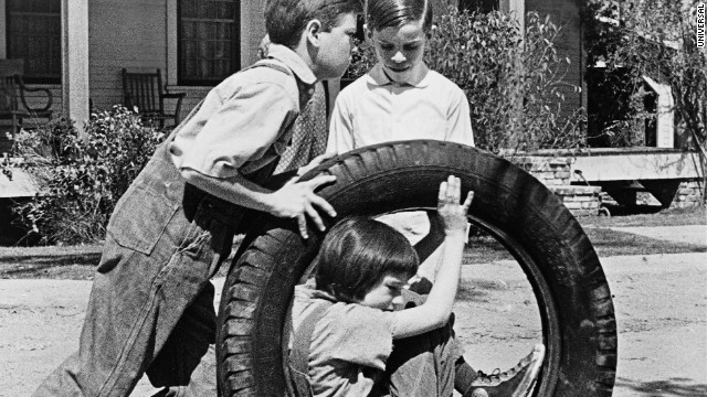 Jem and Dill push Scout in the tire.