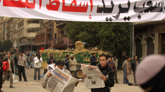 Egyptian anti-government protesters read newspapers under a banner reading 