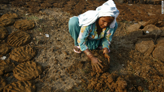  An Indian woman forms patties of cow dung to be dried and used for fuel. Organic waste is also used to power stove as Road to Rio finds out in India.