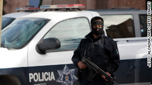 A local police guard a hotel where police are staying in Ciudad Juarez to protect them from attacks by drug cartels.