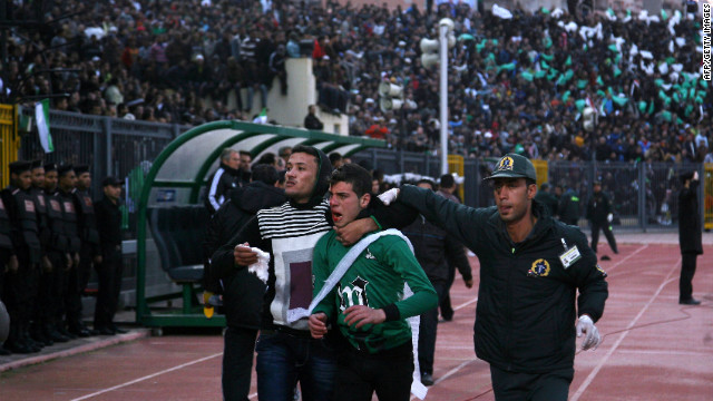 A wounded Al-Masry fan is escorted by a medic and a friend following the clashes.