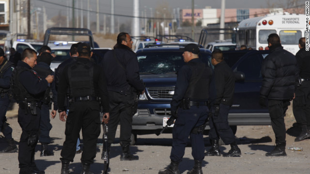 Municipal police officers in Ciudad Juarez, Mexico, collect evidence from a shooting that left colleague Julian Juarez Baena dead