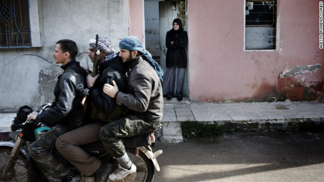 Free Syrian Army rebels ride a motorcycle through Al-Qusayr on January 28. A Corbis Images photographer spent several days in the town. His images offer a rare look at the combat in Syria, where access is limited.