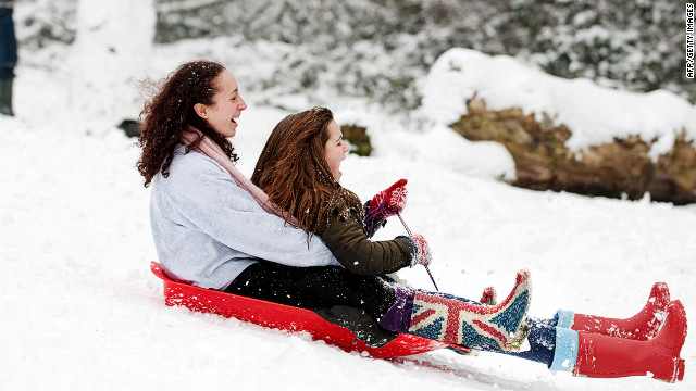 Two girls sled down the hill Sunday in London's Alexandra Park.