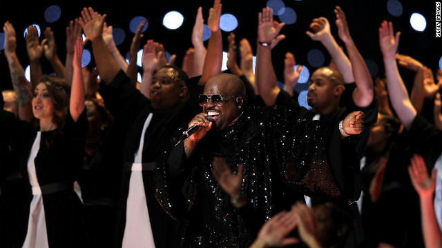 Signer Cee Lo Green performs on stage in a glittery choir robe. Earlier in the show he donned a marching band uniform.