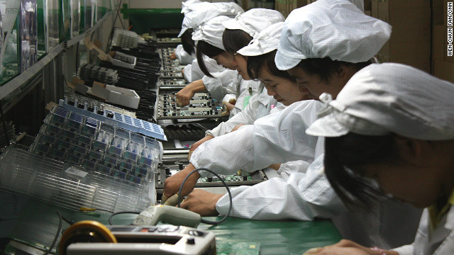 Workers labor on a production line at Foxconn's Longhua plant, which employs 300,000 people and makes products for Apple.