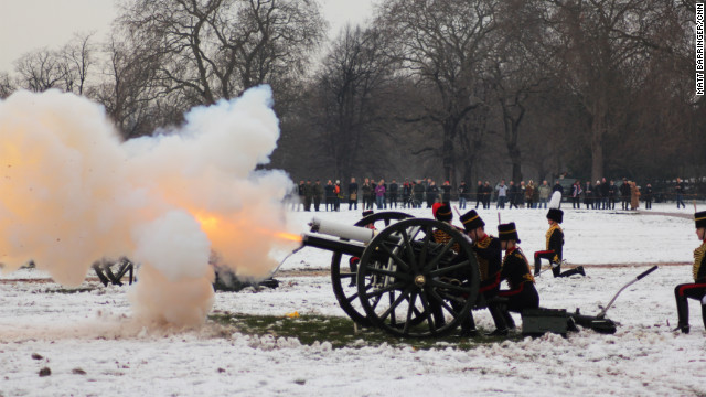 At the stroke of midday, the gunners commence the salute amidst a plume of smoke and muzzle flash.