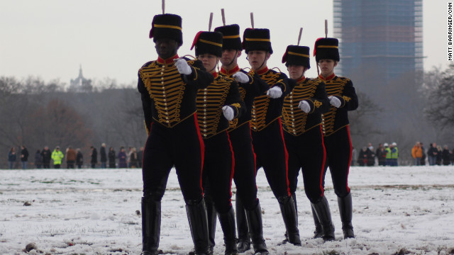 With their army-issue black boots protecting them from the melting snow underfoot, members of the King's Troop march off the field in file.