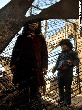 Child looks through a destroyed piano after the 2009 bombing of the school