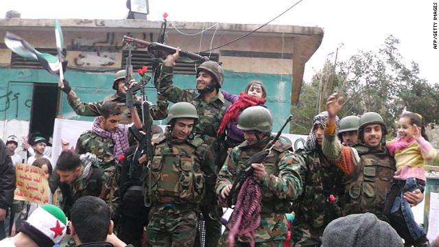 Syrian soldiers who defected join protesters in the al-Khaldiya neighborhood of the restive city of Homs last month.