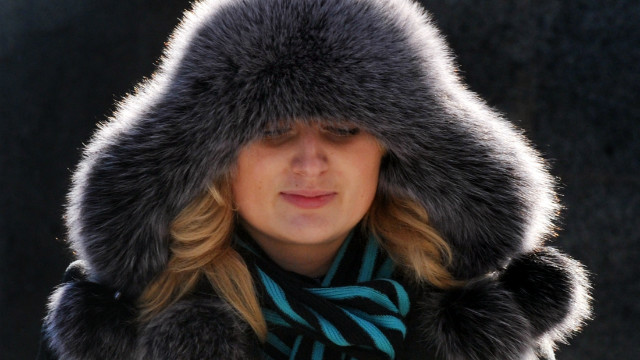 A woman sporting a fur hat walks in the center of Ukrainian capital of Kiev on February 9, 2012. Helicopters ferried food and medicine to iced-in villagers Wednesday as the cold snap tightened its frigid grip on the continent.