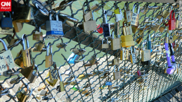 "Allie Roberts took this photo of the ""love locks"" on the Pont de l'Archevêché, known as the Archbishop's Bridge. ""Couples write their names on padlocks, lock them to a bridge over the river, and throw the key in the river, signifying that their love will last forever."""