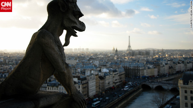 "Kevin Kasmai captured this intriguing view of one of Notre Dame's gargoyle statues overlooking Paris. ""Paris is probably my favorite city in the world. In terms of architecture, places to see, things to do, it's a top destination in my book."""
