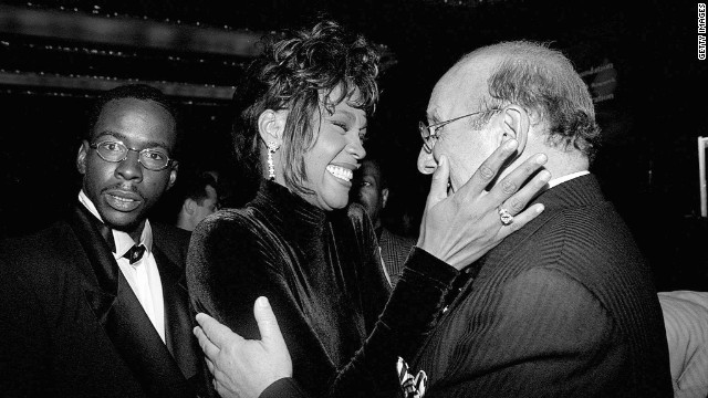 Bobby Brown, left, looks on as his wife, Whitney Houston, congratulates Clive Davis, president of Arista Records, at a 1995 benefit dinner for Davis.