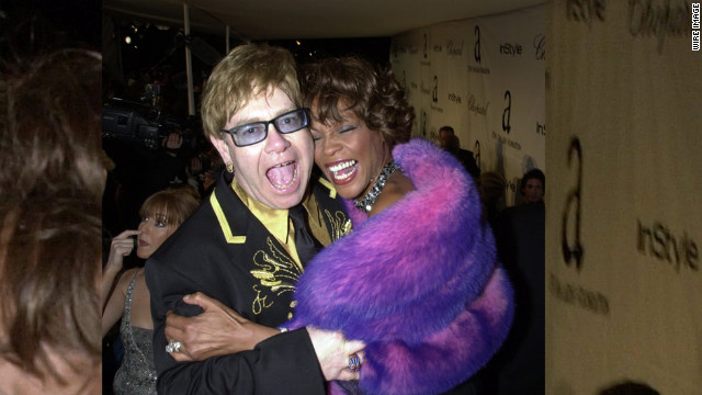 Elton John and Houston embrace during the Academy Awards show in Los Angeles in March 2001. 