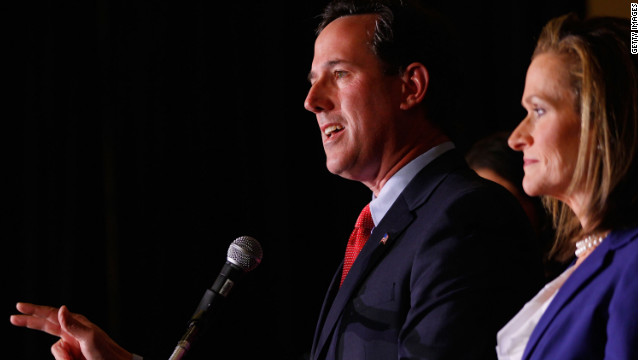 Rick Santorum speaks to supporters as his wife, Karen, looks on. Santorum says Karen wrote parts of 2005 book.