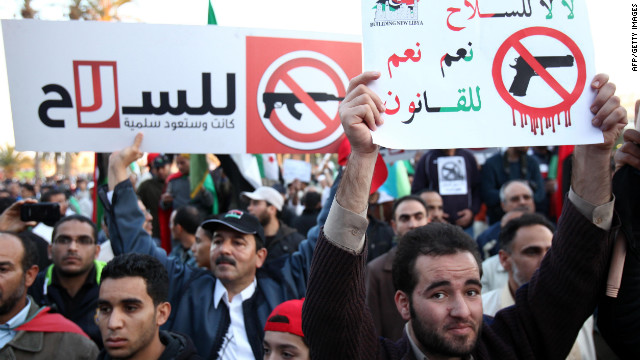 Libyan demonstrators hold banners that read,
