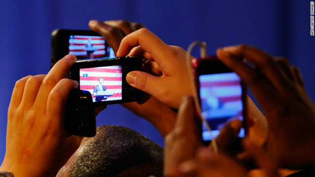 Supporters of U.S. President Barack Obama take pictures with their smart phones.