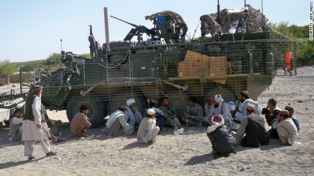 U.S. soldiers shelter in the shade of a Stryker fighting vehicle as they discuss poppy eradication with elders from Barbary Soznay, Afghanistan.