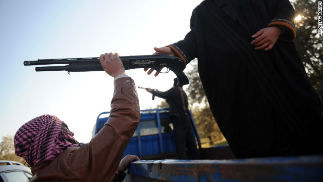 A member of the Free Syrian Army takes his weapon from a comrade during a ...