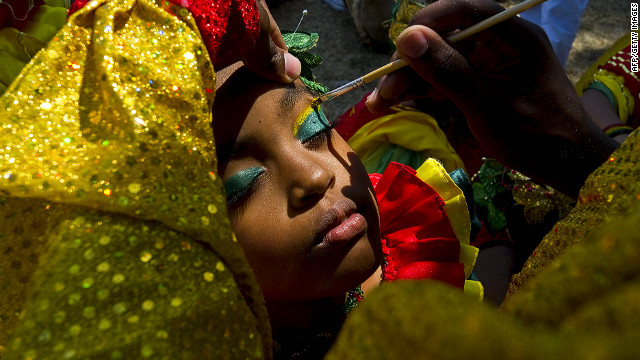A carnival performer has her makeup done before the start of the second-day parade in Barranquilla on Sunday.