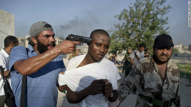 His work was published in Time, Paris Match, Le Monde and the Wall Street Journal.<br/><br/>Photo: Rebel fighters in Tripoli, Libya, captured Africans they accused of being Gadhafi mercenaries.