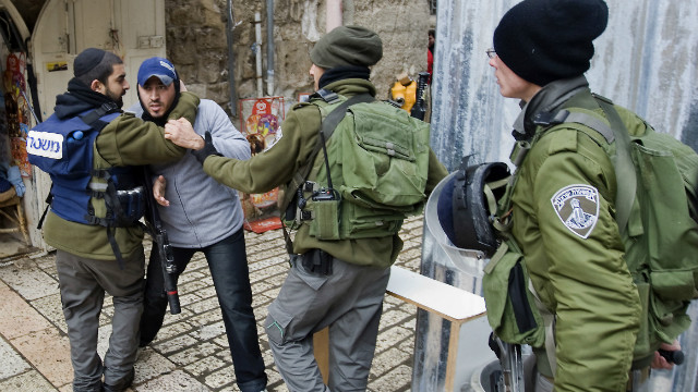 Israeli border policemen detain a Palestinian man outside the al-Aqsa mosque compound on February 19, 2012.