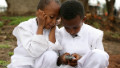 Two boys play with a cellular phone as former U.S. President Bill Clinton tours the Godino Health Center August 1, 2008 in Debre Zeit, Ethiopia.