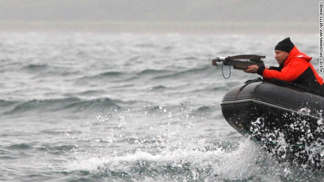The Russian president aims at a whale with an arbalest (crossbow) to take a piece of its skin for analysis at Olga Bay on August 25, 2010 .