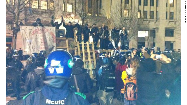 An image taken by an Occupy supporter shows protesters standing on barricades during a police raid, February 27, 2012.