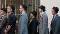 Unemployed young people wear bowler hats as they stand in line outside a job centre in central London during a photocall for the Battlefront Campaign, raising awareness of the large number of young people who are currently unemployed in the UK on October 10, 2011.