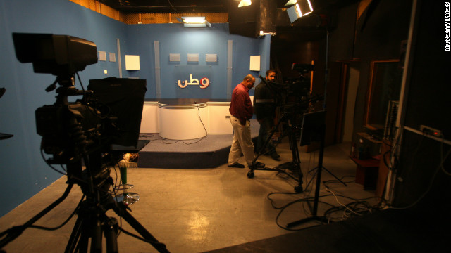 Employees walk through a studio at Palestinian television station