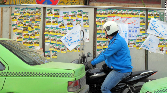 An Iranian motorcyclist looks at parliamentary election posters Wednesday in Tehran.