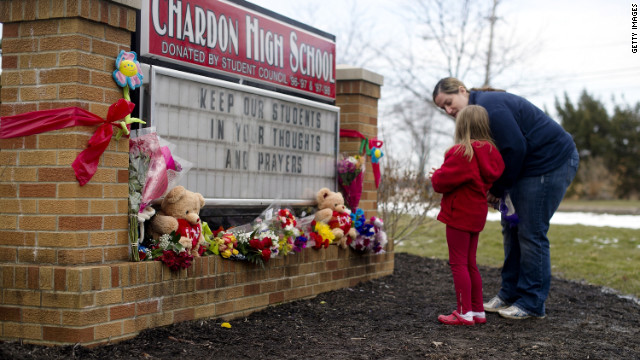 Angela May and her daughter, Eleanore, 5, of Chardon place flowers on the sign outside Chardon High School.