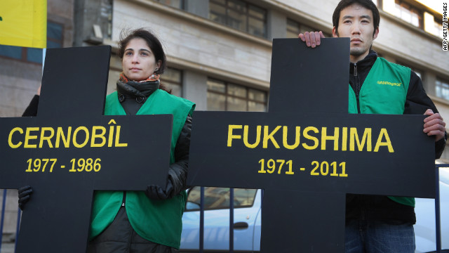 Greenpeace activists hold black crosses. one reading &quot;Fukushima&quot; nuclear power plant and the other, &quot;Chernobyl,&quot; at a protest in Bucharest March 5.