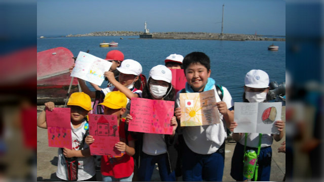 Cards from the project bring bright smiles to the faces of elementary school children in Iwaki City, Japan, as they gathered on the city pier just down from their destroyed school on the four-month anniversary of the earthquake and tsunami.