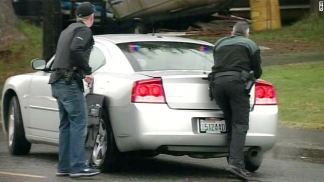Officers take cover outside the courthouse after the stabbing and shooting incident in Montesano, Washington