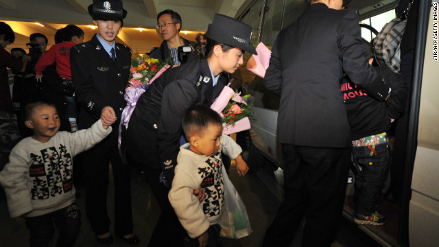 Policewomen lead a group of abducted children recently rescued from child traffickers, as they arrived back home to Guiyang on on October 19, 2011.