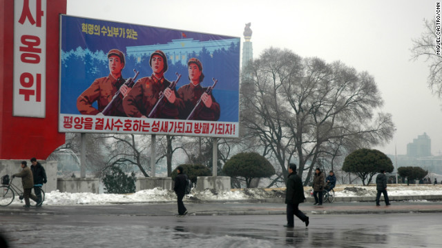 Propaganda billboards tower over passers by in Pyongyang in this image taken in December 2010.