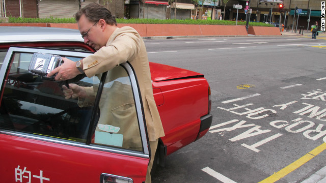 Pieter Franken affixes the Safecast radiation monitoring unit on a Hong Kong taxi.