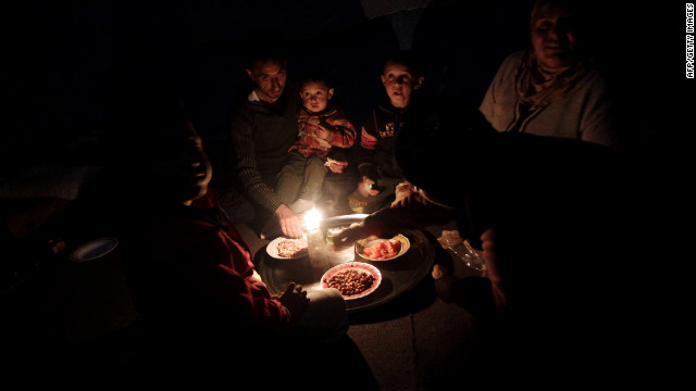 A Syrian family who fled the violence in Homs' Baba Amr neighborhood eats dinner during a blackout at a refugee center.