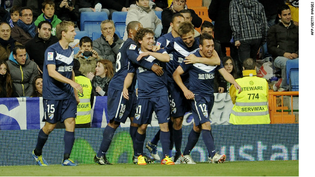 Malaga players celebrate Santi Carloza's last-gasp equalizer against Real Madrid.
